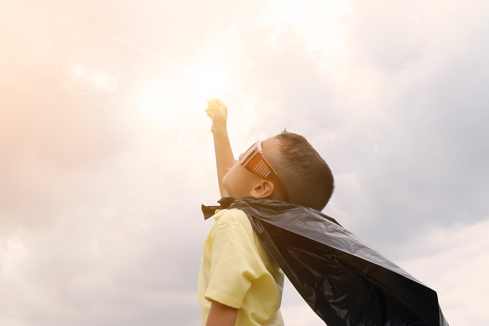 A young boy dressed in a yellow shirt with a black cape. He's holding one hand up in a superhero pose, toward a cloudy sky.