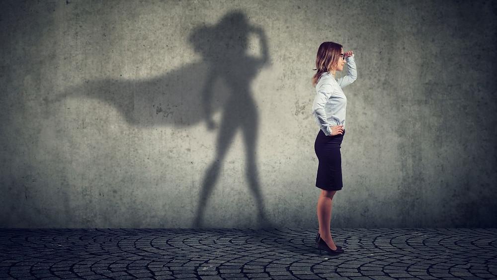 Monochrome photo of a women looking ahead. Her shadow looks like a super hero.