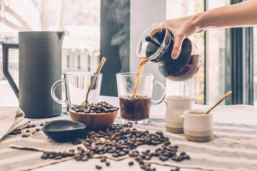 Mesa com grãos de café, e uma xícara sendo servida com a bebida.