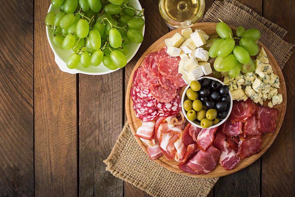 Tábua de petiscos com diferentes tipos de embutido, contendo: uvas verdes, salame, bacon, queijo gorgonzola e queijo brie.