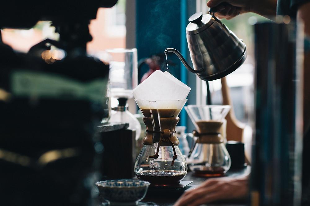 Pessoa coando café através do filtro de papel, com uma jarra de água quente sendo despejada.