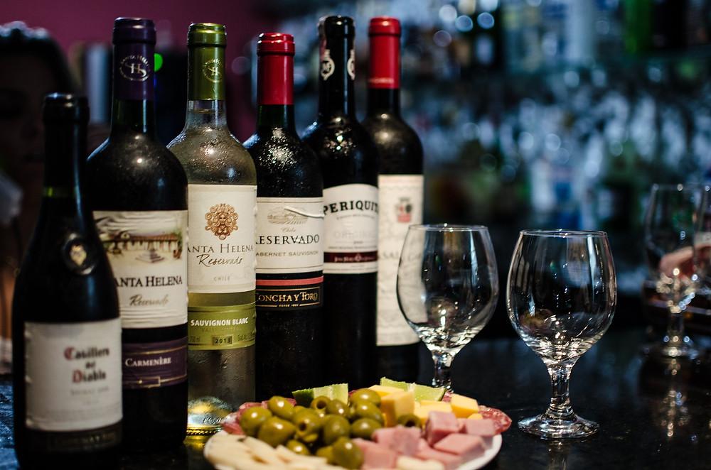 Mesa com duas taças e 6 diferentes garrafas de vinho, com petiscos para acompanhar vinho junto, em especial, azeitonas, presunto, queijo e limão.