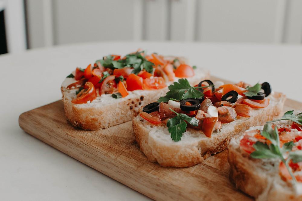 Imagens de bruschetta com pão italiano, tomate e azeitonas. Opção de petisco para acompanhar vinho.