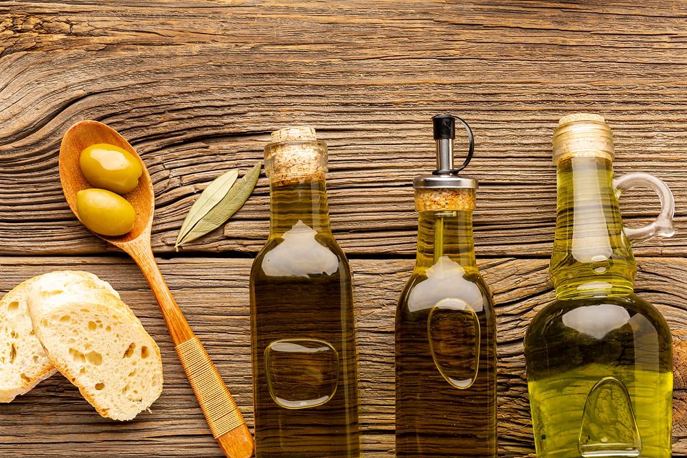 Diferentes tipos de azeites em diversos vidros também diferenciados ao lado azeitonas e pão.