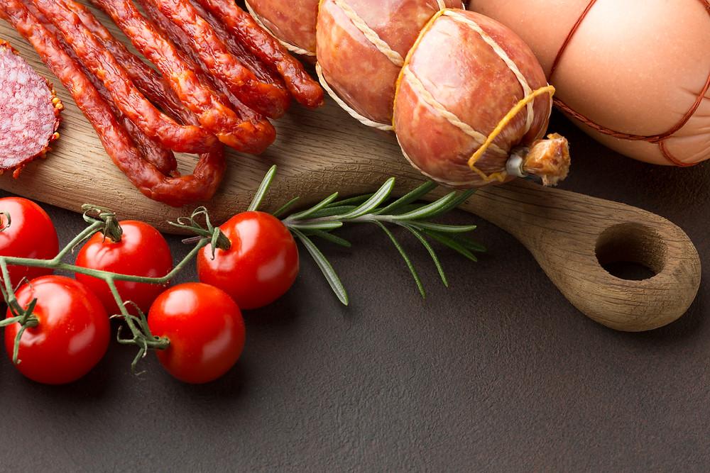 Imagem com diferentes tipos de embutido, contendo também tomate cereja, alecrim, linguiça, mortadela e salame.