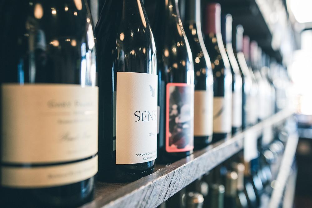 Prateleira de madeira com diversas garrafas de vinho que mostram as principais diferenças entre vinhos.