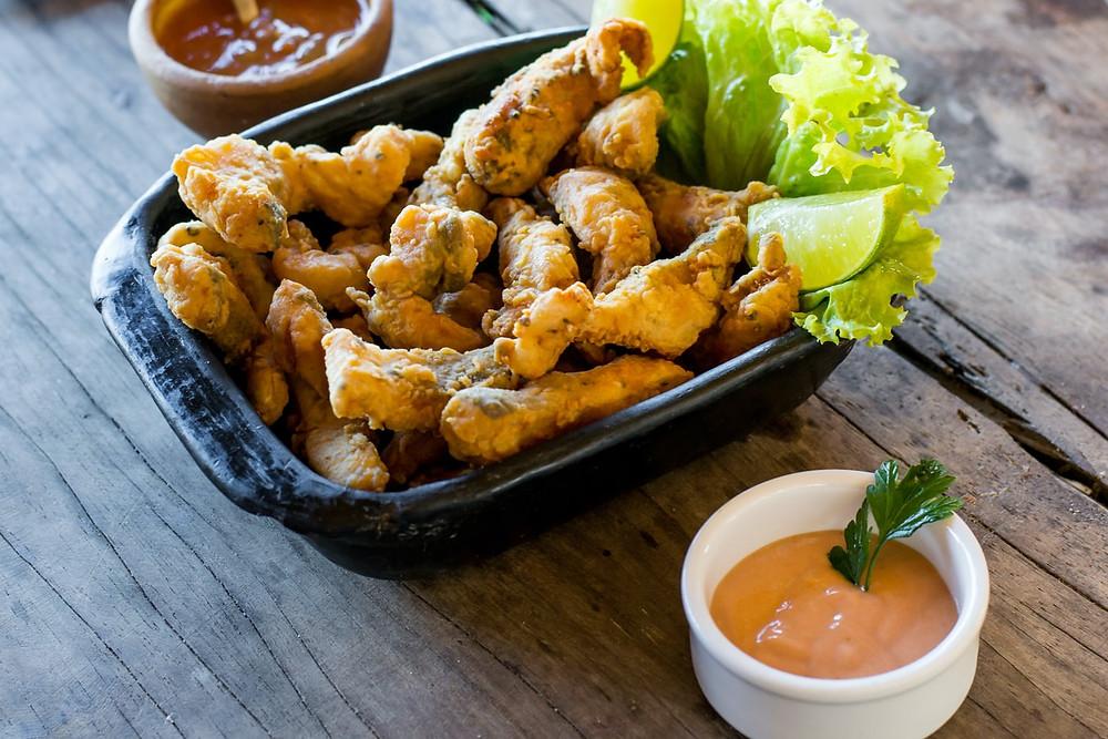 Porção de peixe frito como opção de petiscos para acompanhar vinho. Na imagem, temos também dois diferentes tipos de molho e folhas de alface com um pedaço de limão.