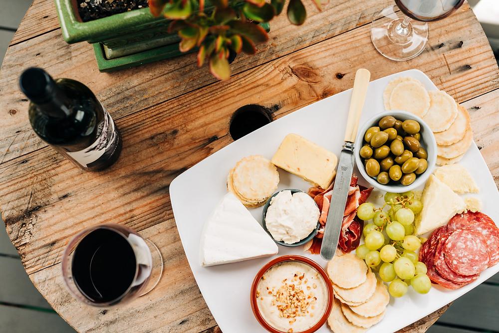Mesa com petiscos para acompanhar vinho, junto a uma taça de vinho tinto. Os petiscos presentes na mesa são: azeitonas, uvas, salame, torradas, patê e queijos.