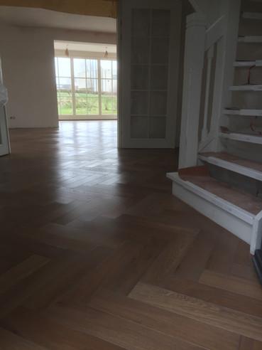 Eiken Visgraatlamel, vast verlijmd op cementdekvloer met vloerverwarming. Afgewerkt met Royl kleur 16, Shell Grey
