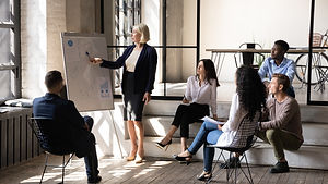 Serious middle aged businesswoman mentor coach corporate leader pointing on flip chart giv