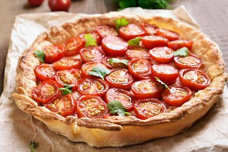 Tomato pie on baking paper, close up vie