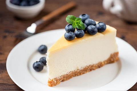 Cheesecake with blueberries on white pla