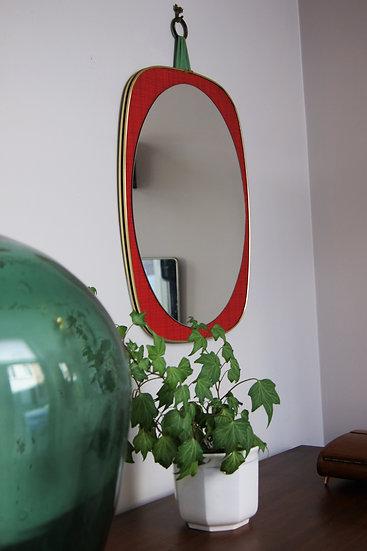 Miroir ovale sur fond rouge