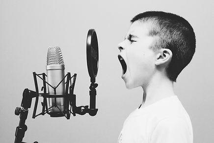 boy singing on microphone with pop filte