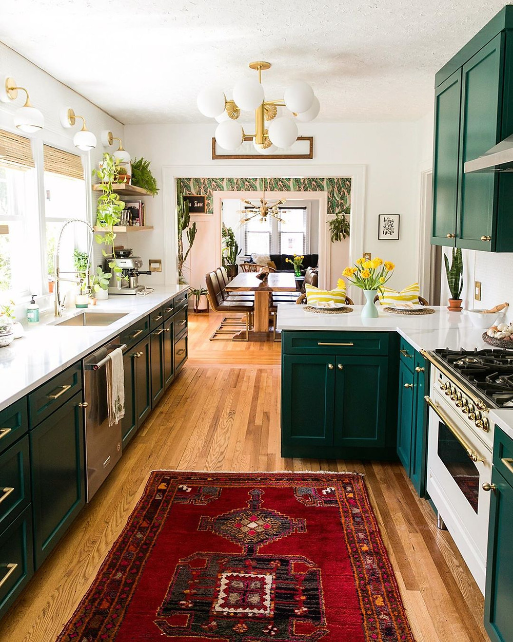 open kitchen space with green cabinets and red rug