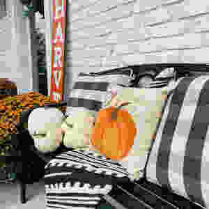 Front porch with a black bench filled with plaid and pumpkin decorative pillows and a throw blanket