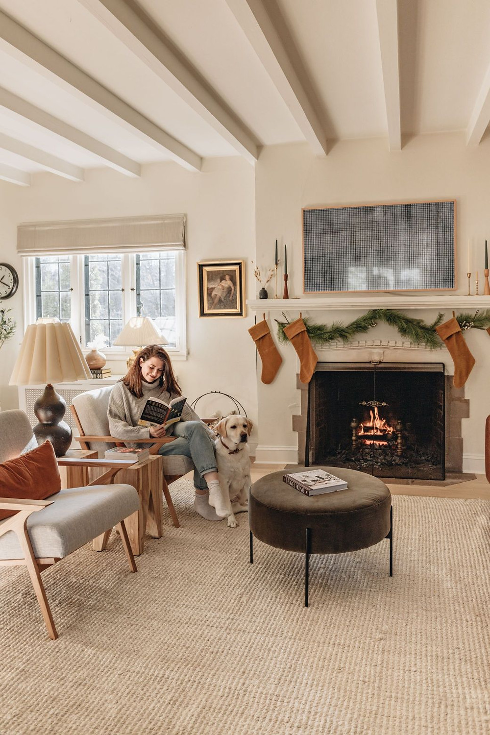 A woman reading a book on a gray and neutral wood sitting chair in front of a lit fireplace with orange stockings and a green garland across the mantle.