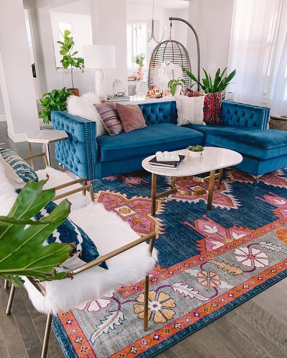 stunning teal sofa and blue rug in a boho dream living room with a lot of plants