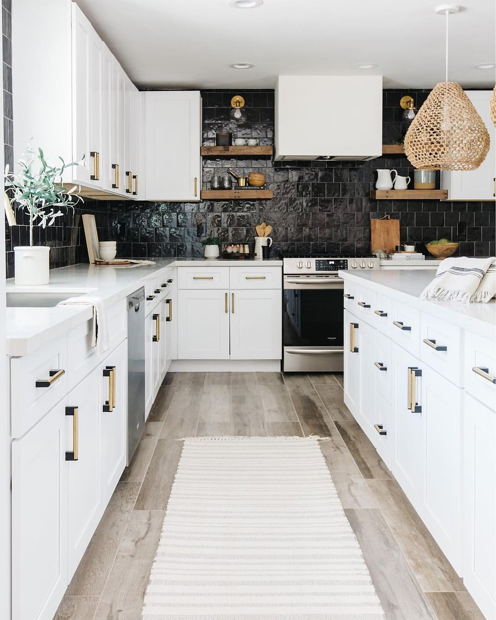 A white kitchen with black backsplash tiles and grey hardwood flooring