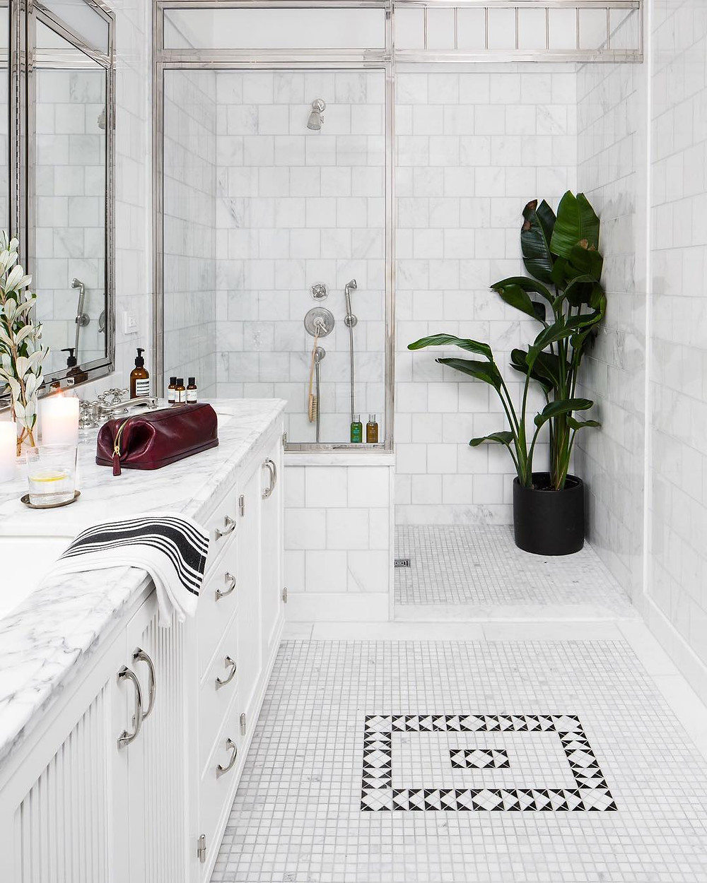 Glam bathroom design with white marble countertops, marble shower tiles, and white tile flooring