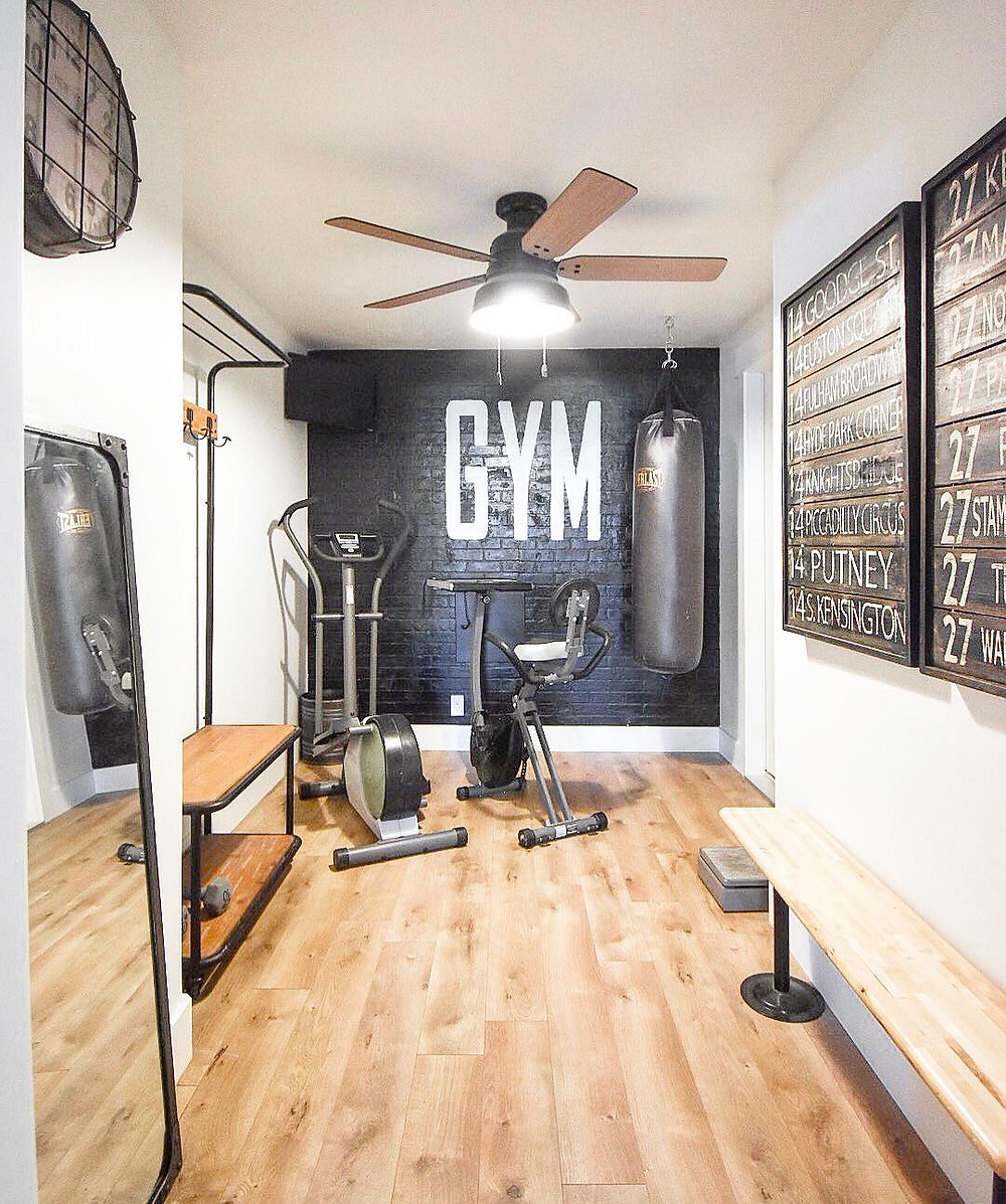 bright home gym with black walls and punching bag