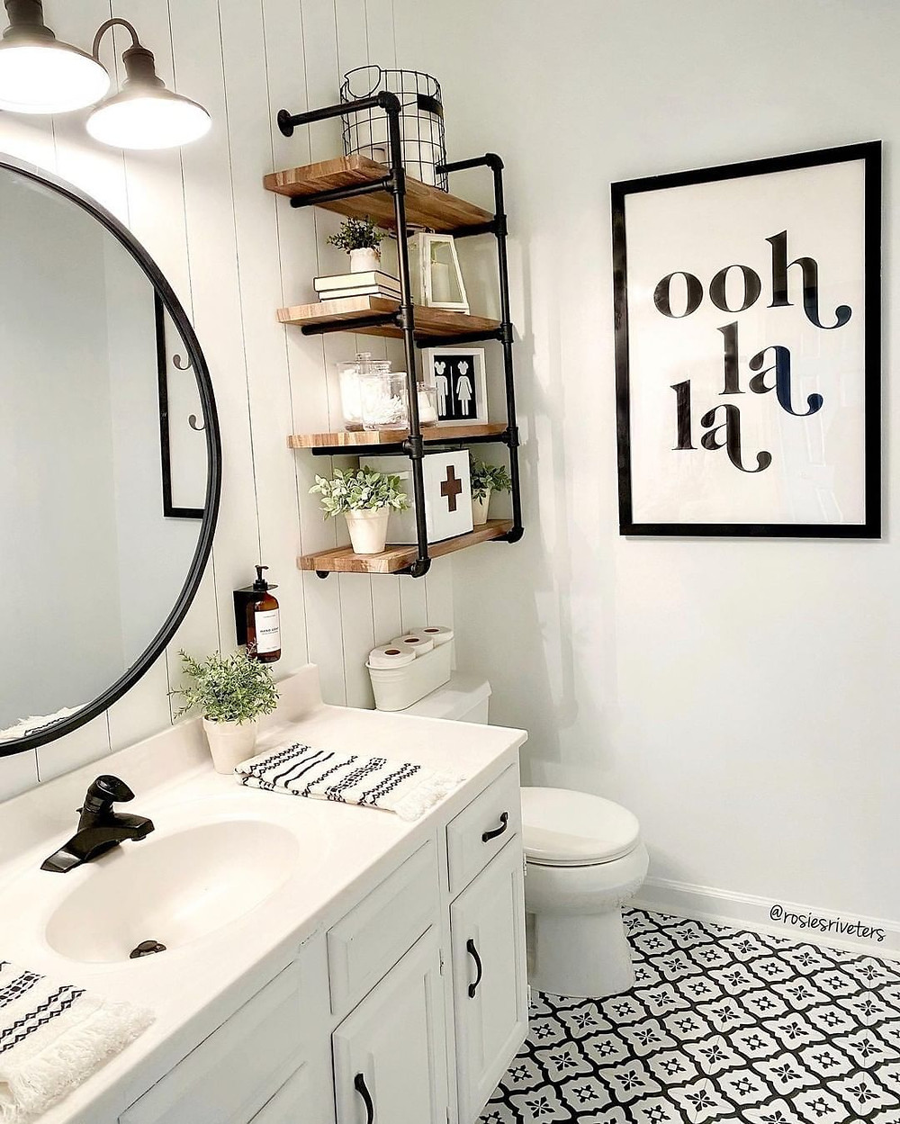 black and white bathroom with tile flooring, abstract art and circle mirror