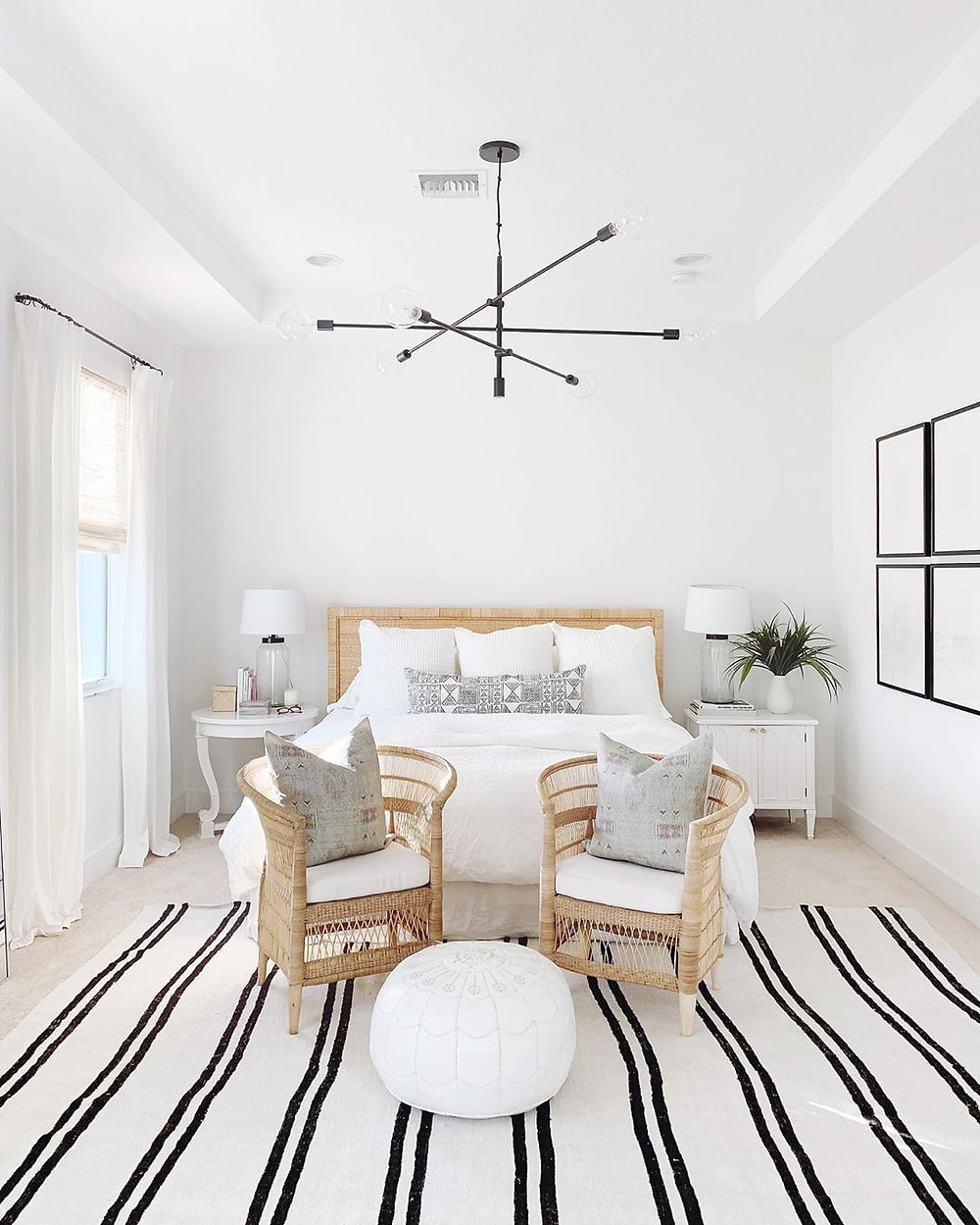 White bedroom interior design with striped area rug, ottoman and natural wicker chairs