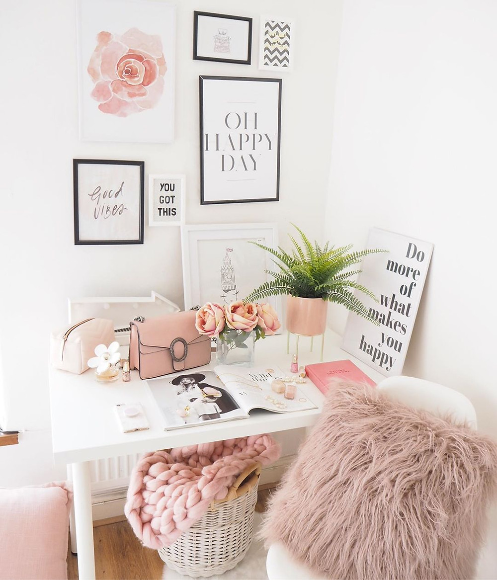 Motivational posters in a white interior design home office with pink accents