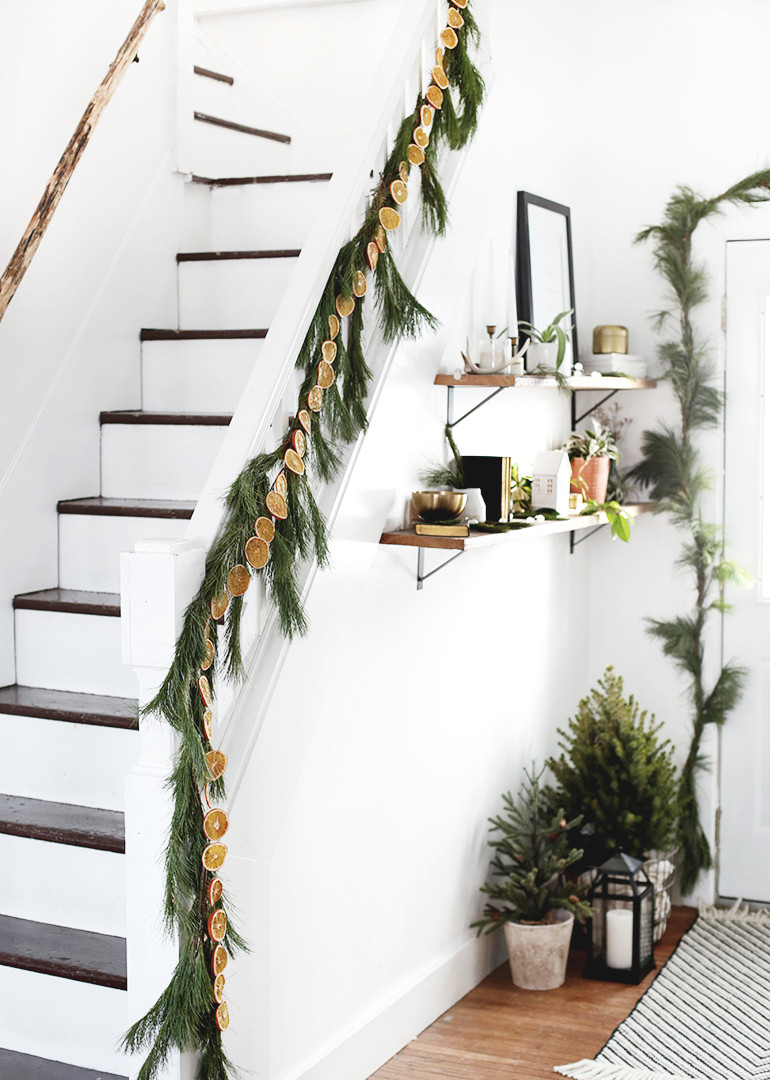 White and dark wooden stairs decorated with a dried orange garland next to the entryway of the home with open shelving and home decor accessories.