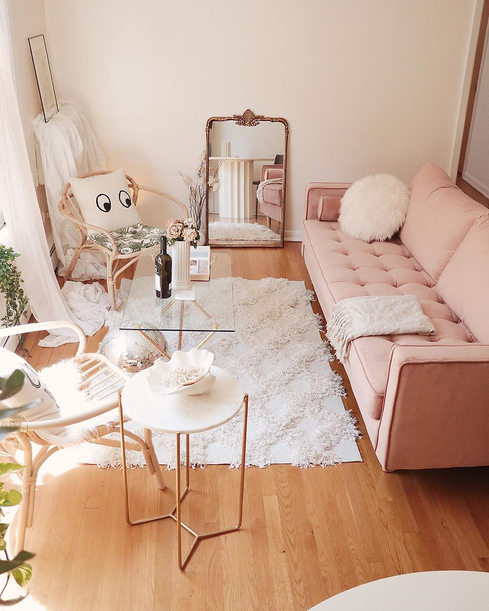 pink boho living room with sofa and floor mirror