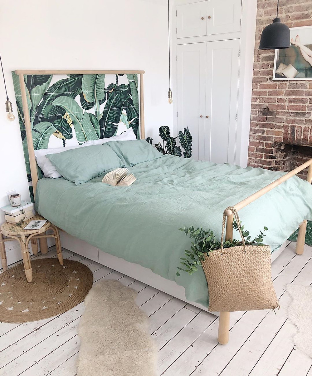 mint green bedroom sheets with wooden bed frame and brick wall