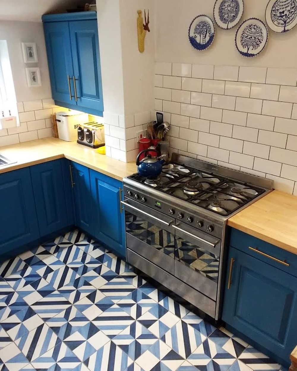 blue tile flooring with blue cabinets, wooden countertops and subway tiles in stunning kitchen design