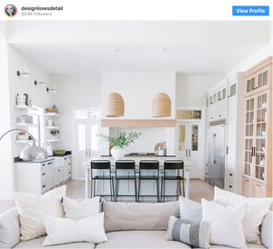 Large white kitchen with island and black bar stools behind cozy sofa filled with pillows from Mollie Openshaw's Instagram