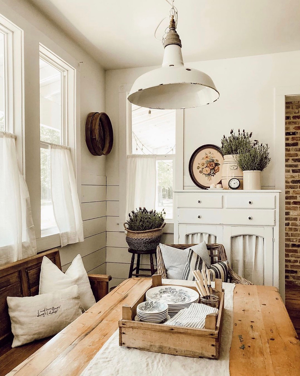 Farmhouse interior design dining room with wooden table, wooden bench, house plants, and a rustic lighting fixture