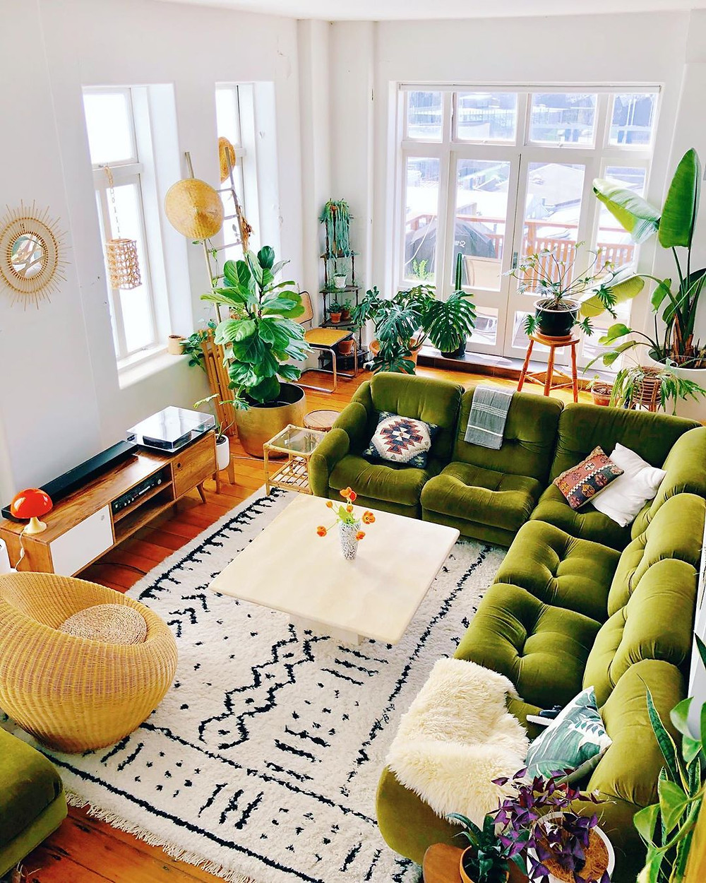 living room with white Moroccan rug, green sofa, and tons of nature and plants