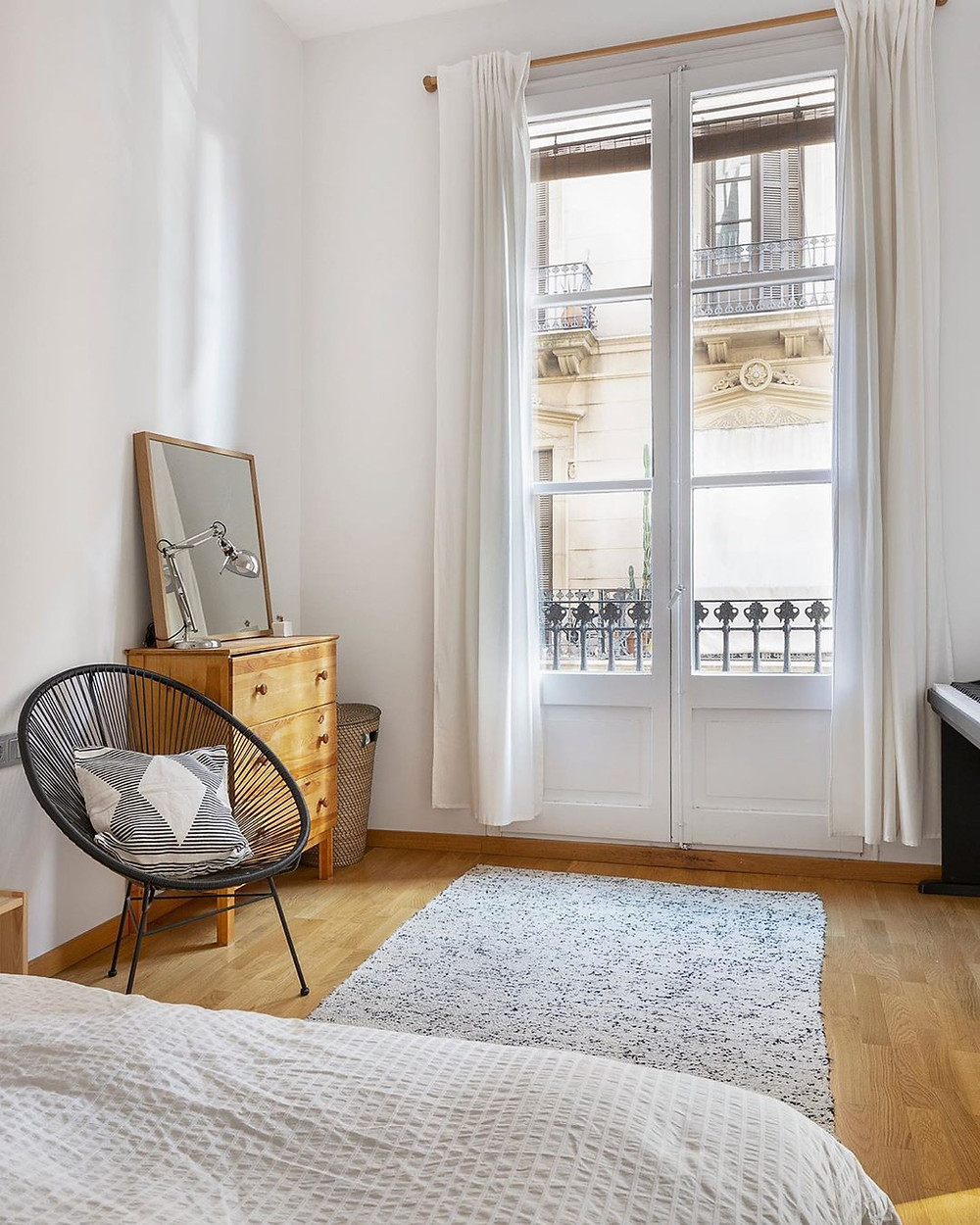 simple bedroom decor by the window with wooden dresser
