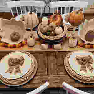 A traditional Thanksgiving table setting with an array of pumpkins as a centerpiece on a kraft table runner.