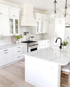 a white kitchen with marble countertops with a luxurious feeling and black sinks