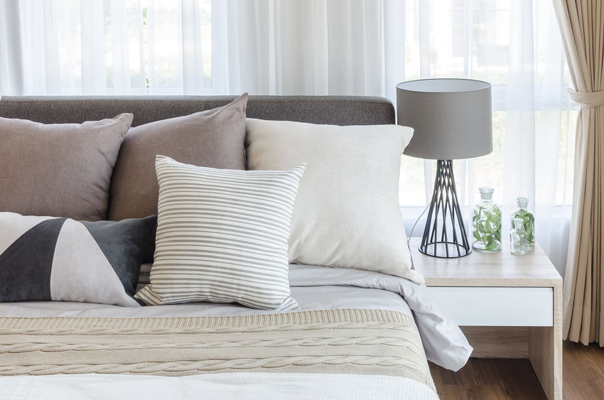Close up of a cozy made bed with decorative pillows next to a nightstand with a gray lamp