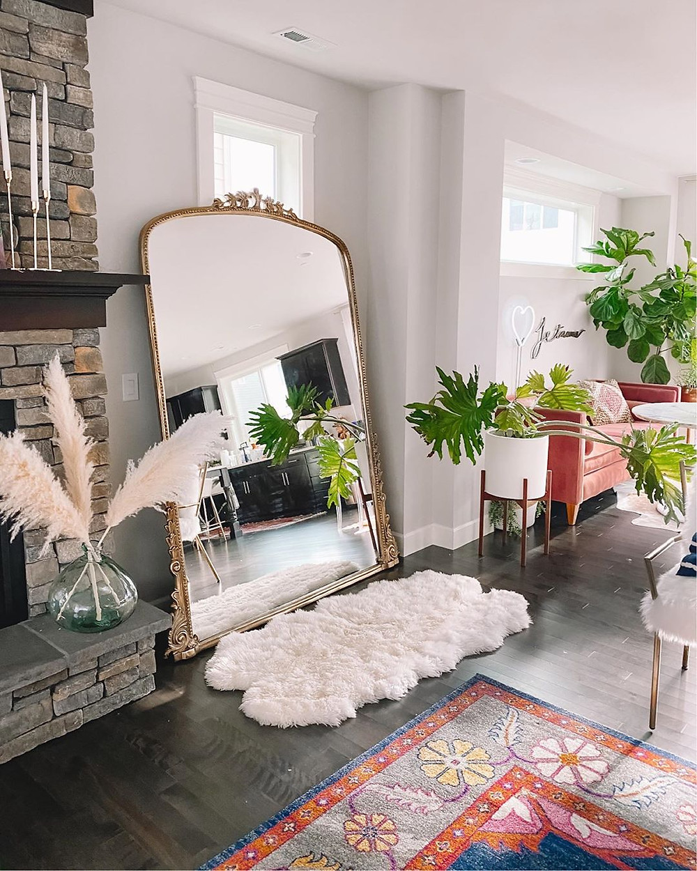 boho living room with golden floor mirror and vintage rug
