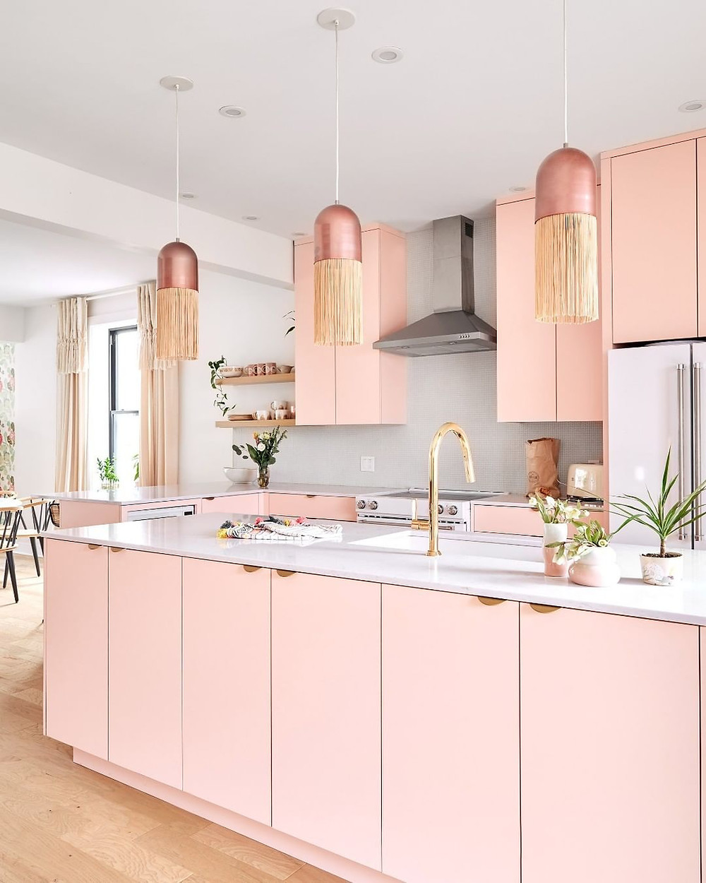 Glamorous pink kitchen with unique hanging lights and golden sink