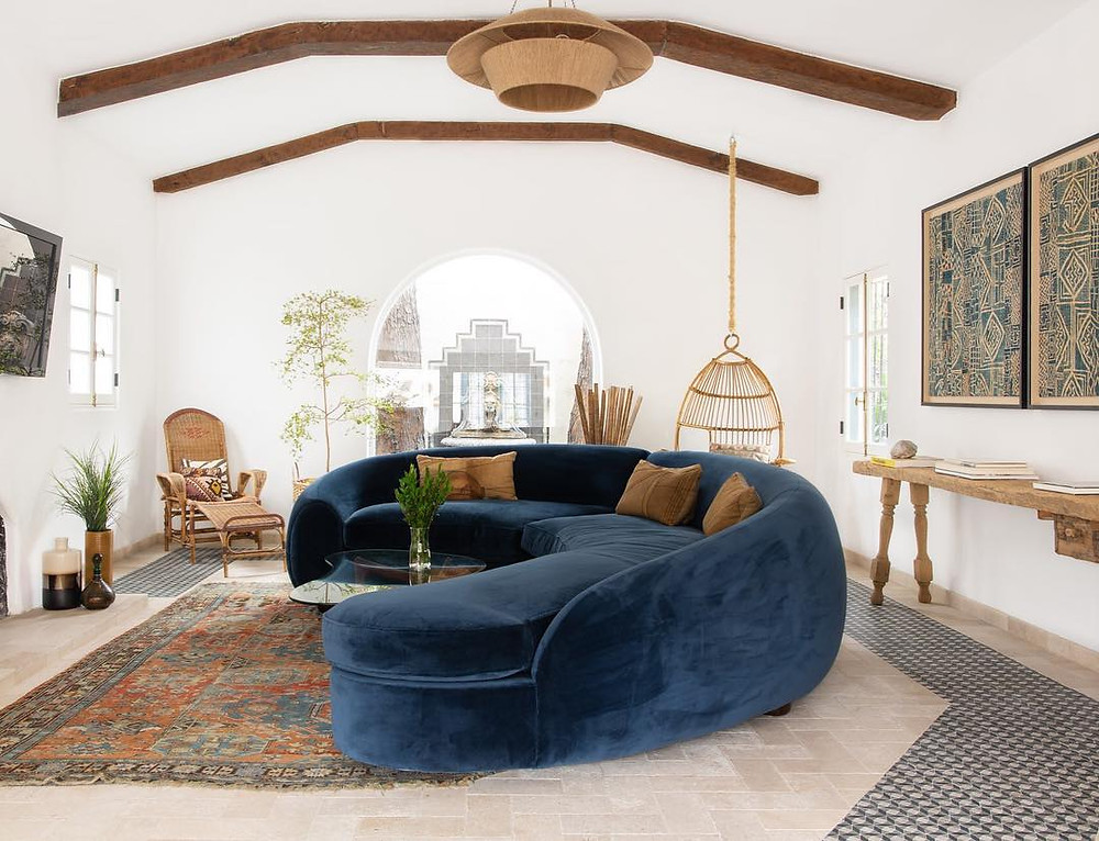 large luxury curved blue sofa with vintage rug, exposed head-beams and natural woven furniture