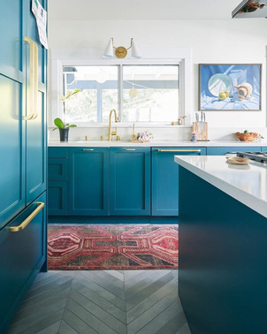 turquoise blue kitchen decor with white countertops and red tribal rug