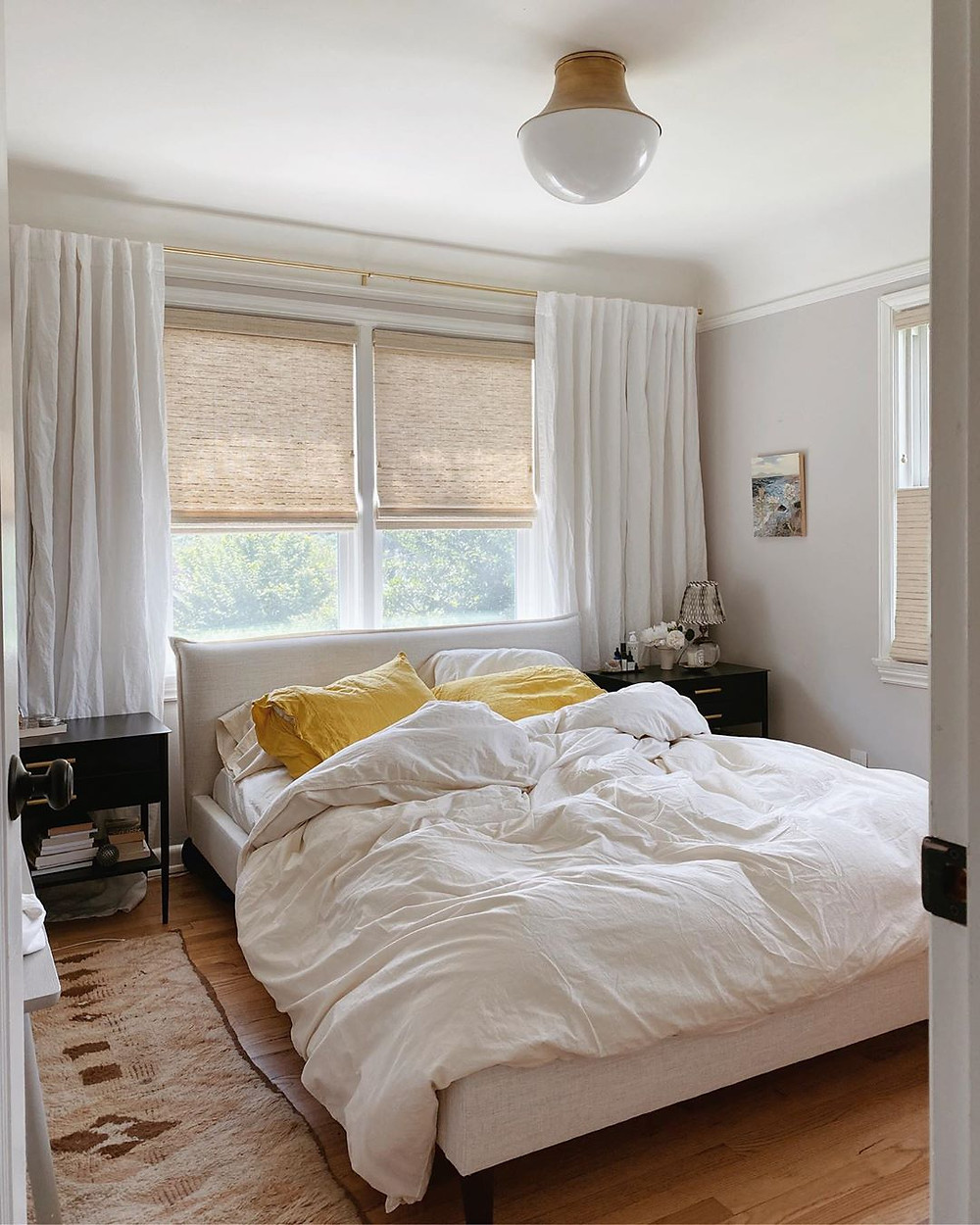 cozy bedroom with yellow pillows and white bed sheets