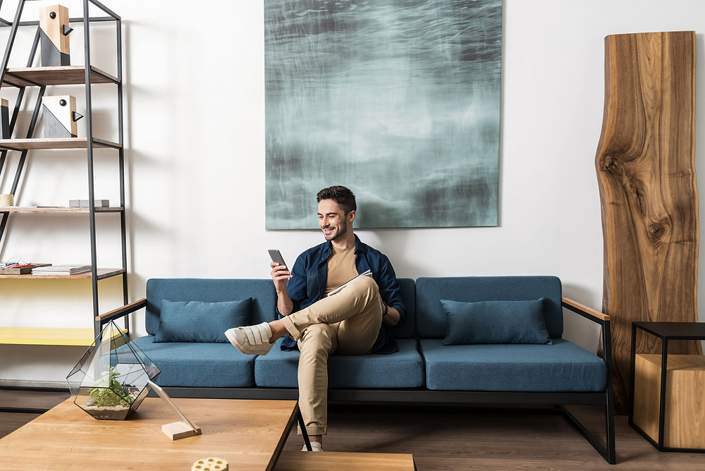 man using smartphone relaxing on sofa playing game on phone and smiling