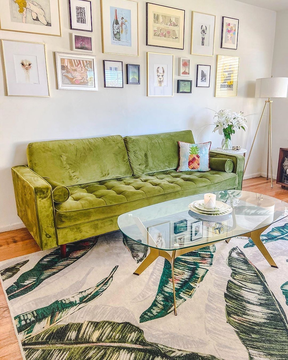 tropical living room with mid century decorations, green sofa and wall gallery