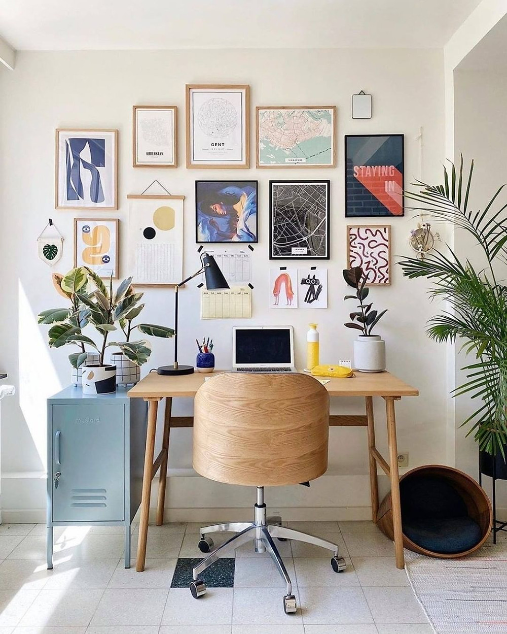 wooden desk and chair in a home office setup with tons of wall art and photography