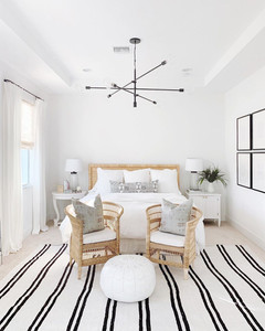 white bedroom with striped rug and bright decor