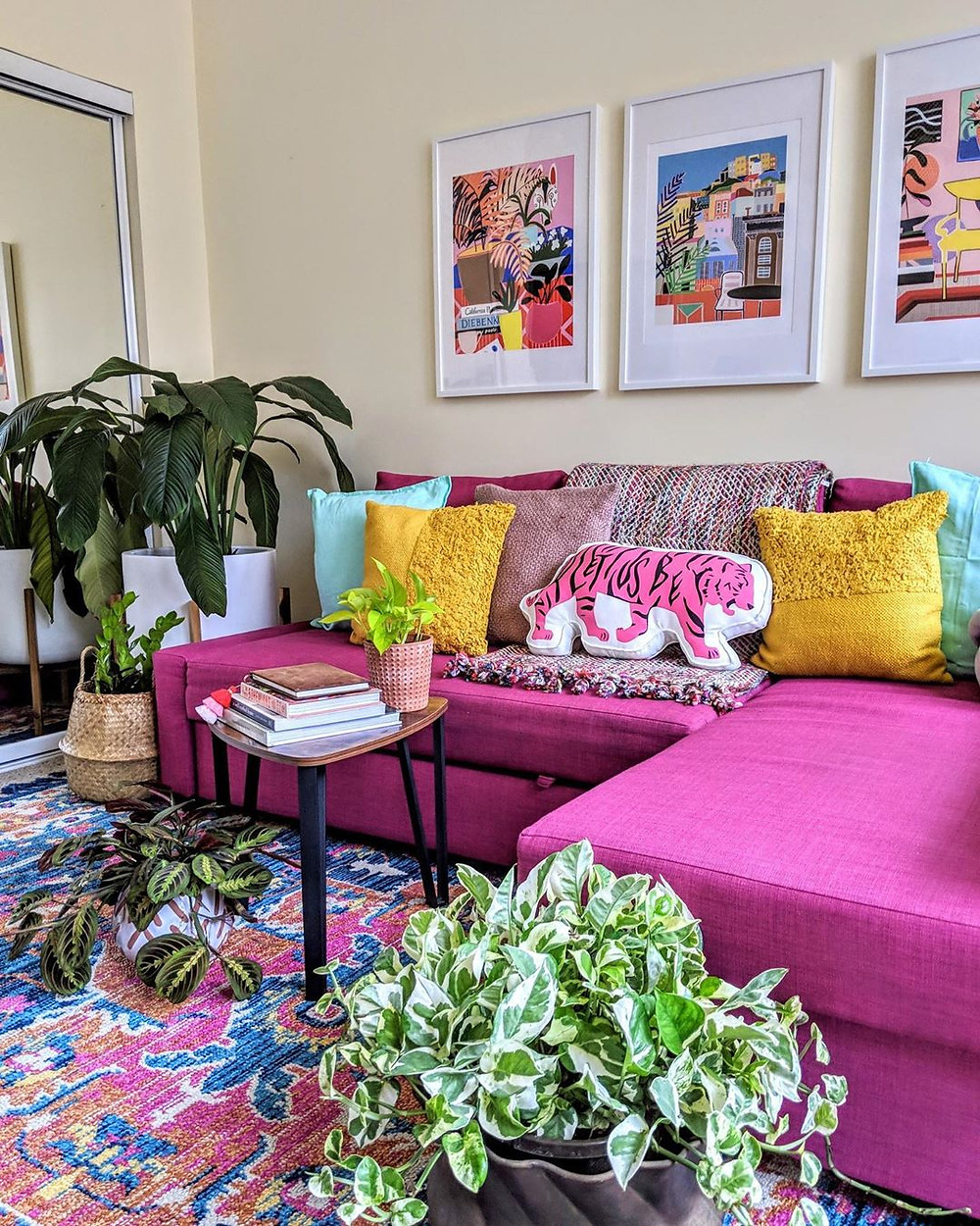colorful eclectic living room design with vibrant rug and artwork and pink sofa