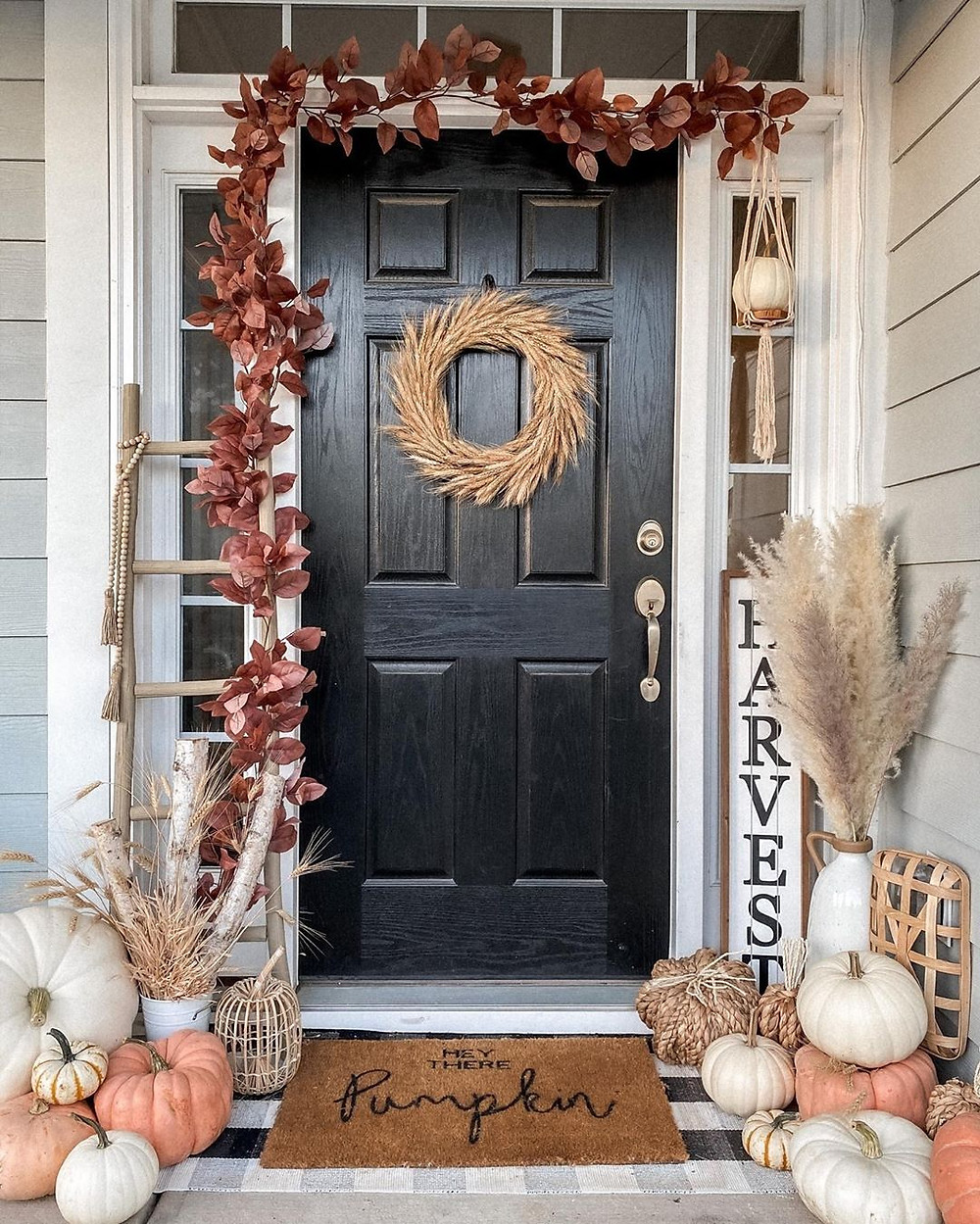 black front door entryway decor with wreath, pampas, pumpkins decorated for autumn